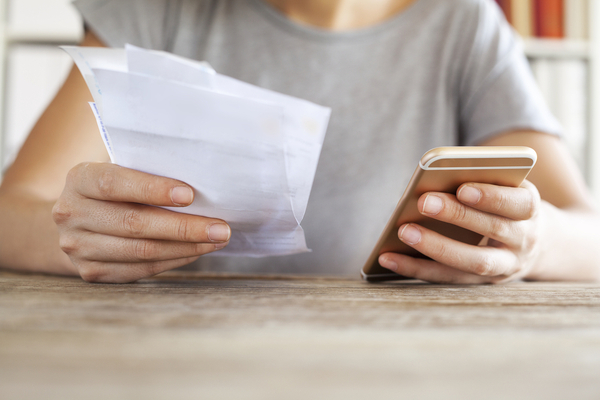Woman hands with bills and mobile phone
