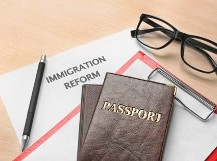 Passports and sheet of paper with words IMMIGRATION REFORM on table